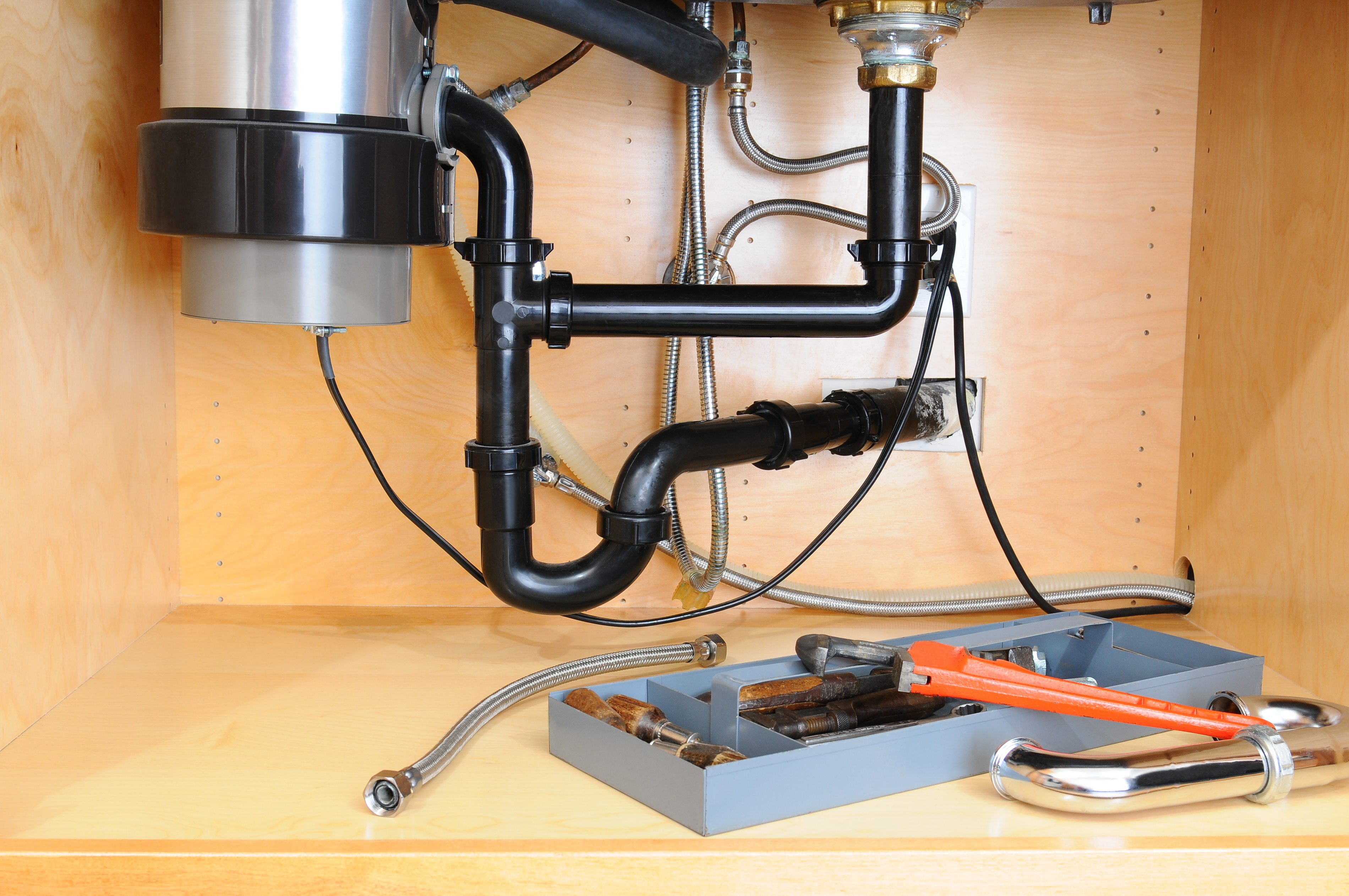 Detail of the plumbing system under a modern kitchen sink